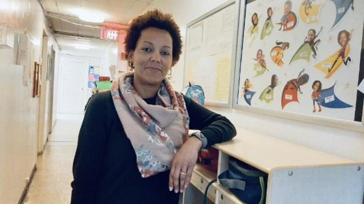 Thérèse Musafiri pose debout dans un corridor et sourit au photographe.