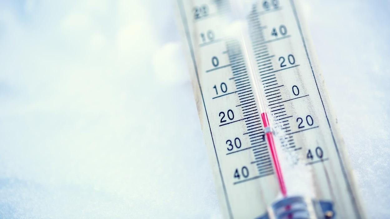 Un thermomètre affichant -20 degrés Celsius sur de la neige