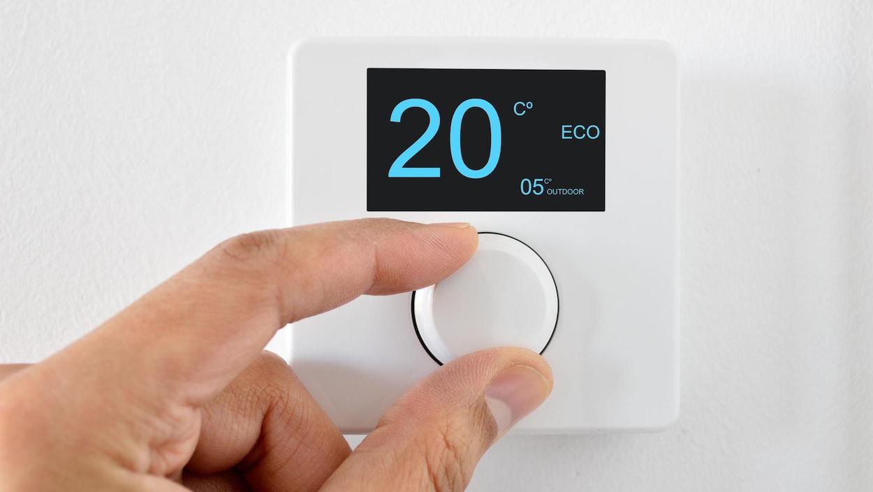 Une personne règle un thermostat mural.