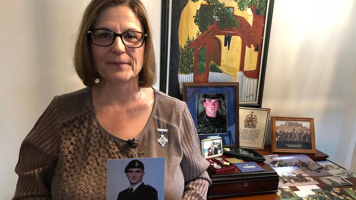 Une femme portant une croix d'argent honorifique qui tient une photo d'un jeune homme en habit militaire est debout dans une table sur laquelle se trouvent des photos et des souvenirs du jeune homme.