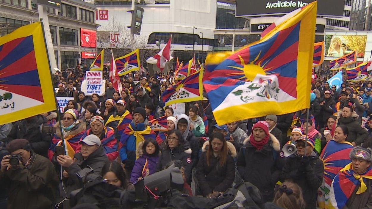 Une foule de manifestants arborant des drapeaux tibétains.