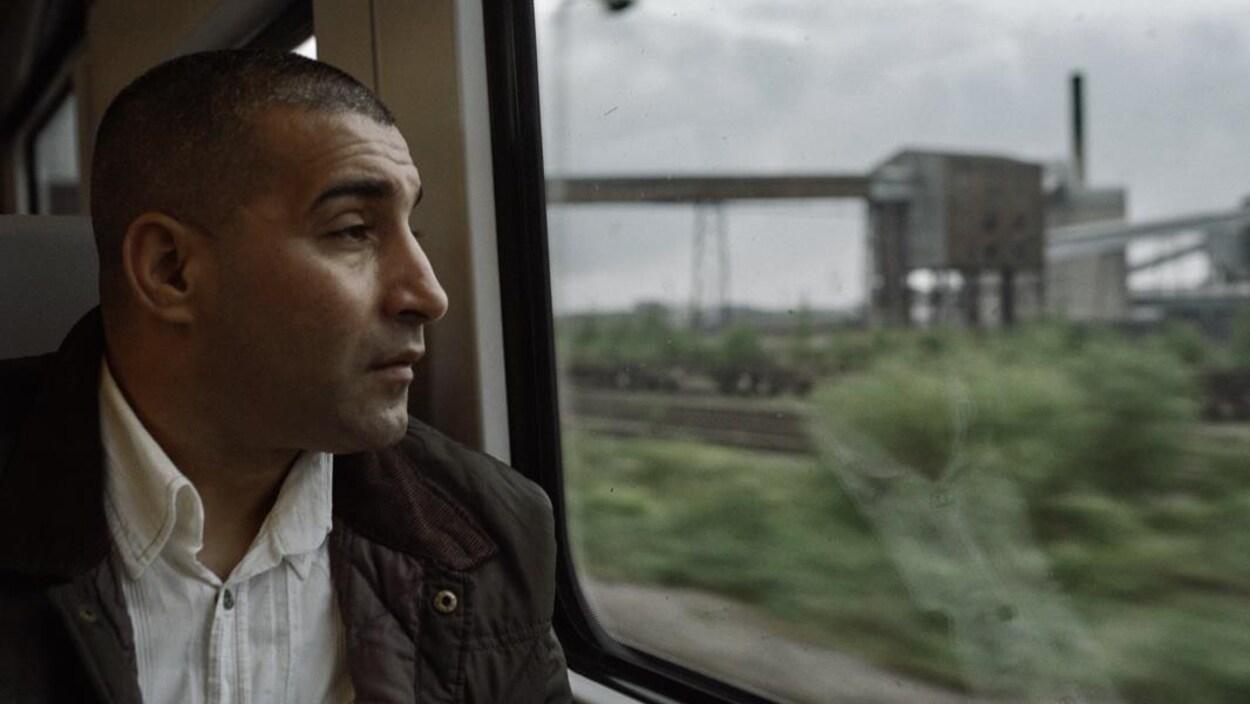Un homme assis dans un train regarde au dehors par la fenêtre.