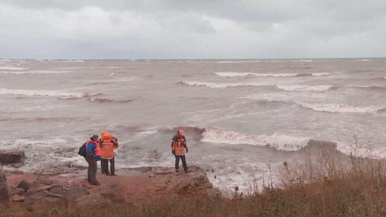 Trois personnes sur la côte regardent vers la mer