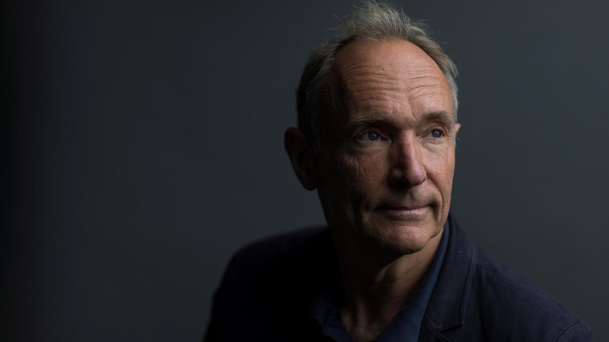 Une photo de Tim Berners-Lee, un homme aux cheveux gris avec une légère calvitie portant un veston bleu marine. Il regarde vers la droite d'un air pensif.