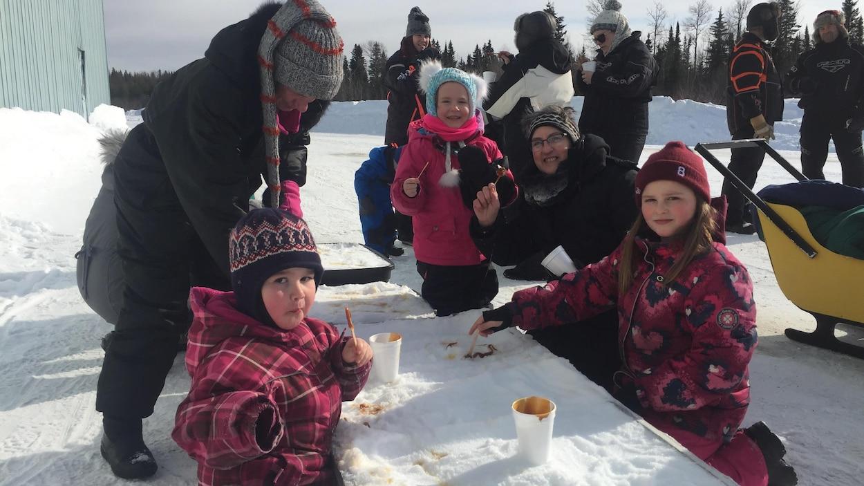 Des enfants et des parents qui dégustent de la tire sur la neige.