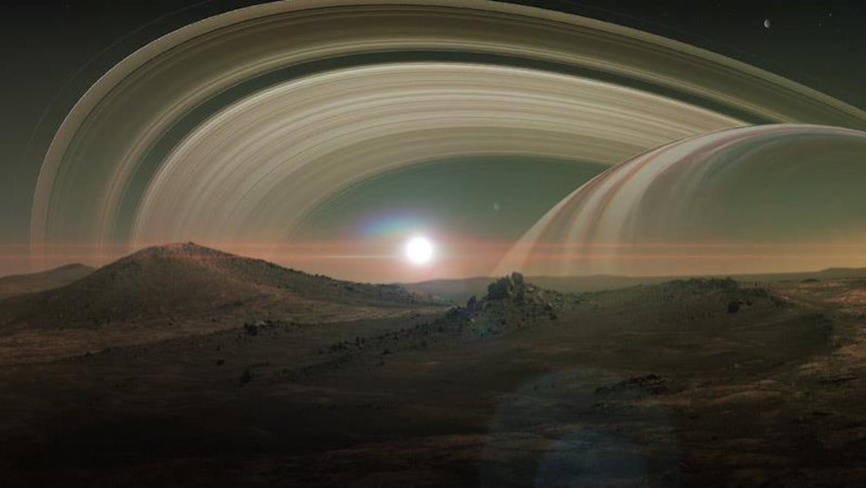 Impression artistique de la surface de Titan, avec en arrière plan les anneaux de Saturne.