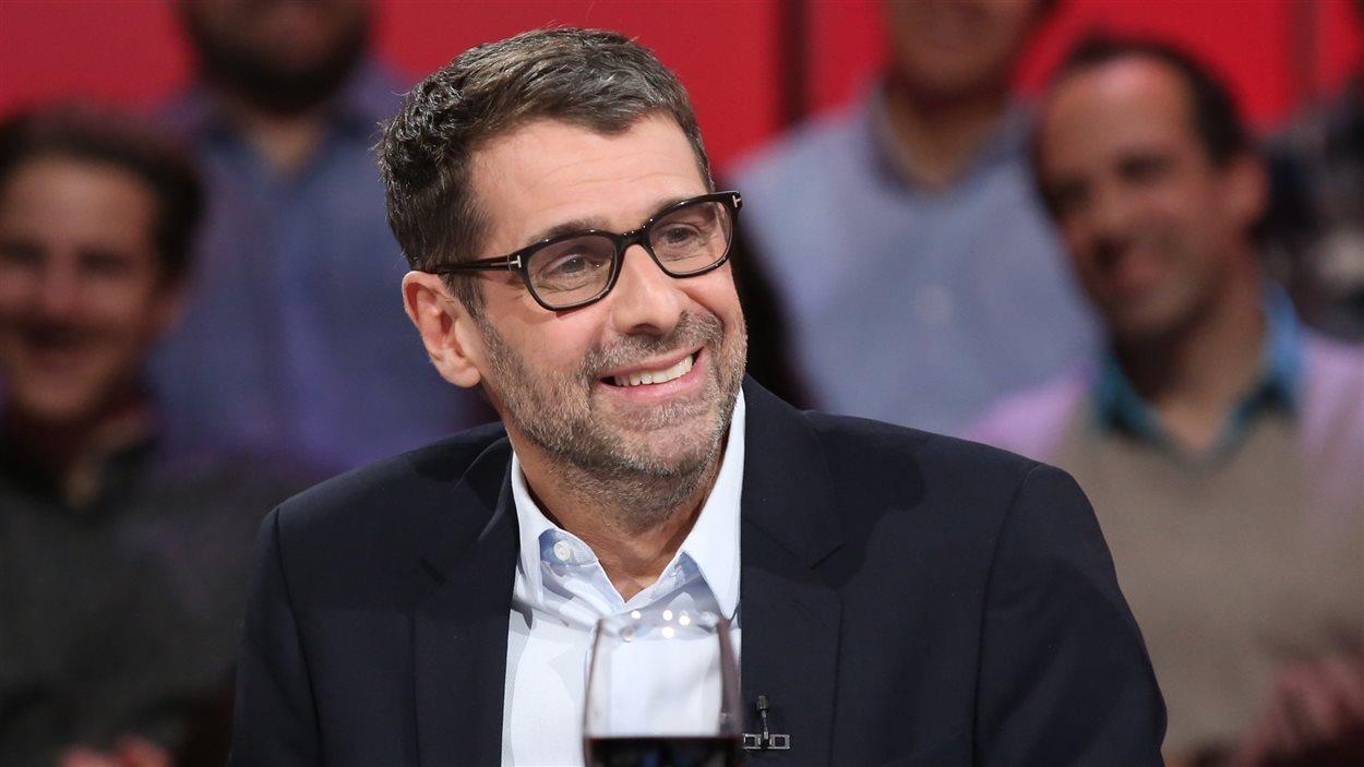 Un homme avec des lunettes et les cheveux grisonnants est assis devant uen foule, dans un studio de télévision.