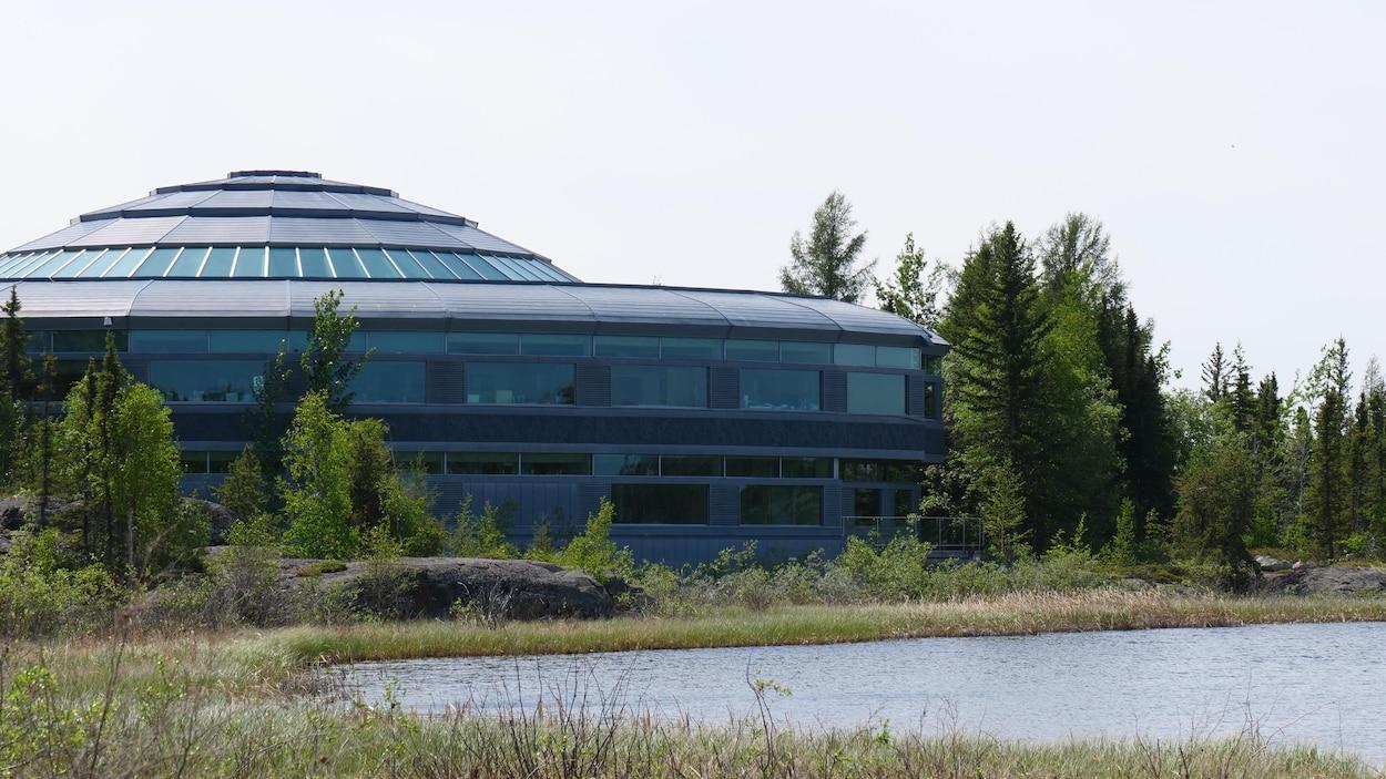 Un bâtiment en forme de dôme à côté d'un lac.
