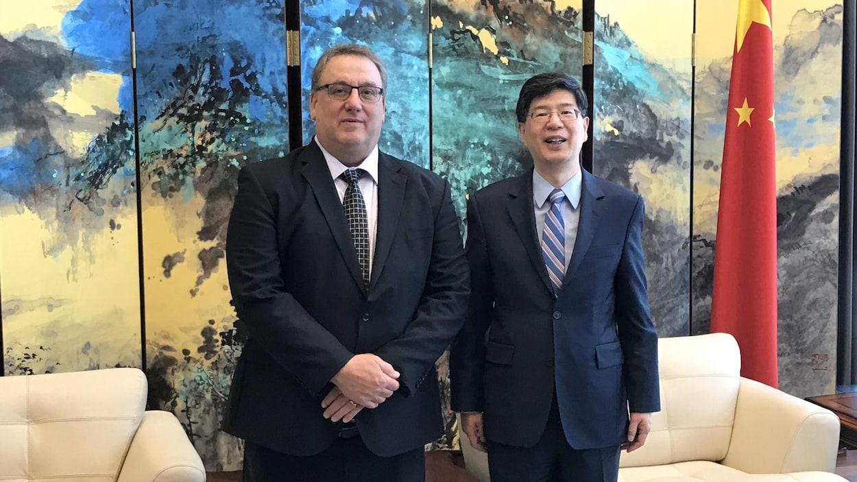 Deux hommes avec à leur gauche le drapeau chinois.