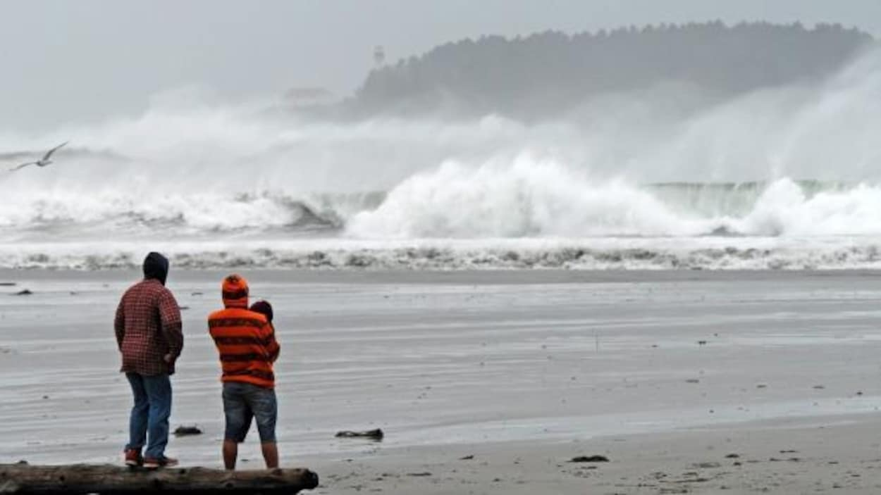 Un couple observe de grosses vagues se briser sur la plage Chesterman à Tofino en Colombie-Britannique