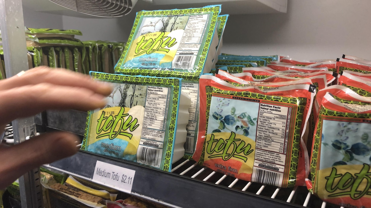 Une main s'approche de paquets de tofu entreposés dans un réfrigérateur.