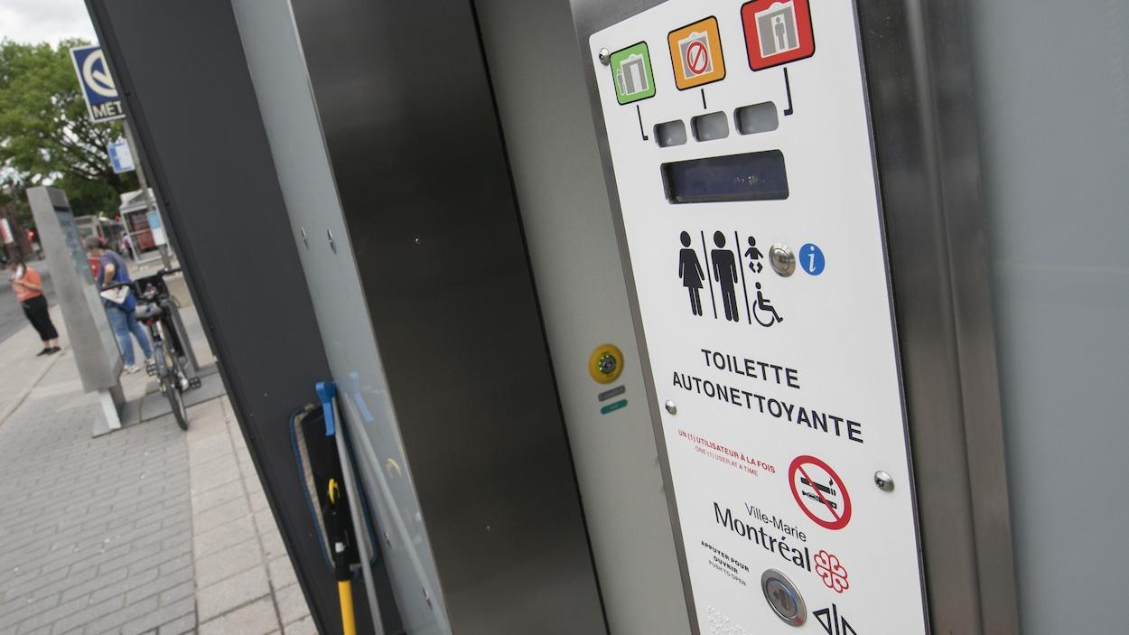 Un panneau montre que ces toilettes publiques peuvent être utilisées par les hommes, les femmes, les personnes handicapées et qu'elles comportent une table à langer.