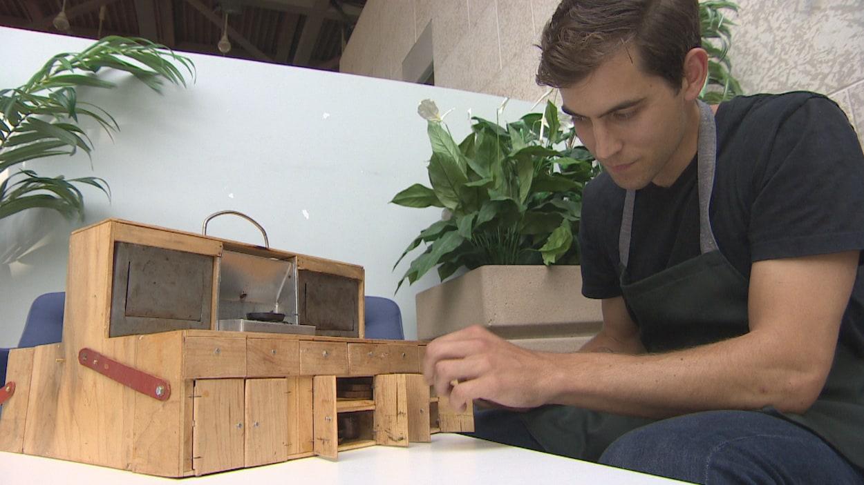 Tom Brown assis avec sa mini-cuisine en bois.