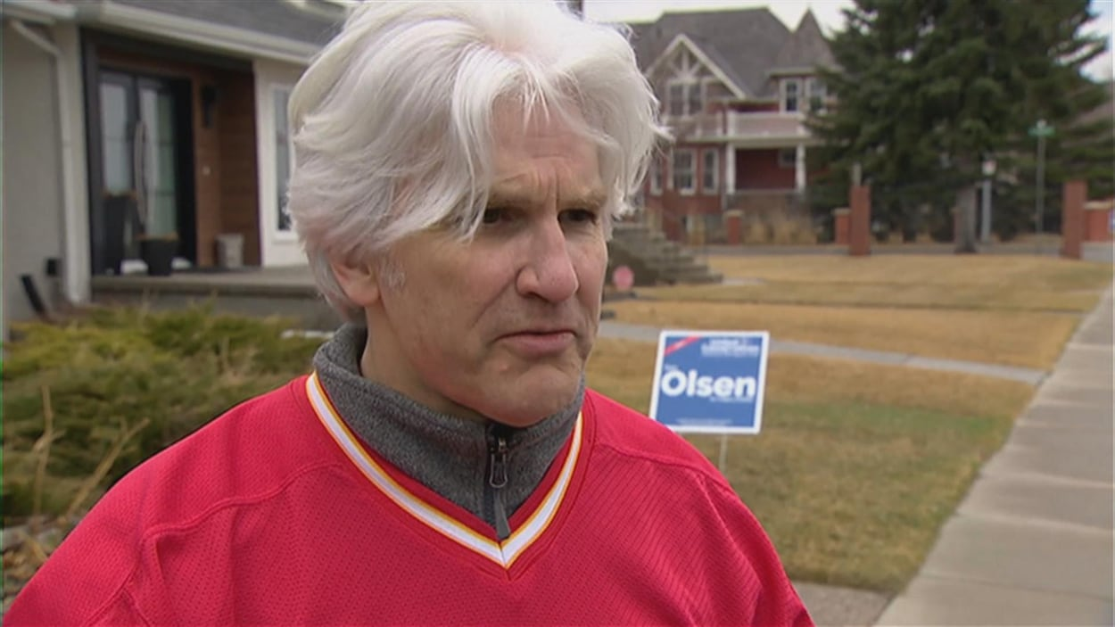 Tom Olsen, qui a des cheveux blancs et porte un chandail de hockey, parle à la caméra, dehors. Derrière lui, il y a une affiche électorale avec son nom.