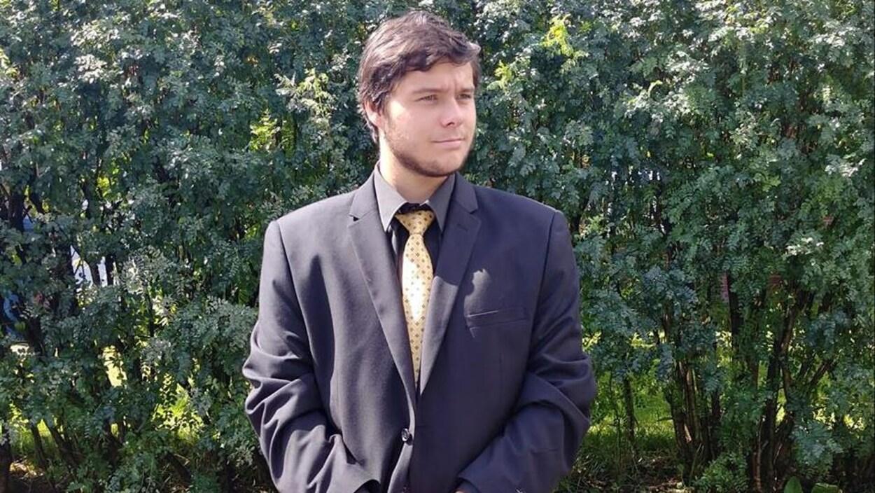 Un jeune homme porte un veston bleu et une cravate jaune.  Il pose devant la caméra.