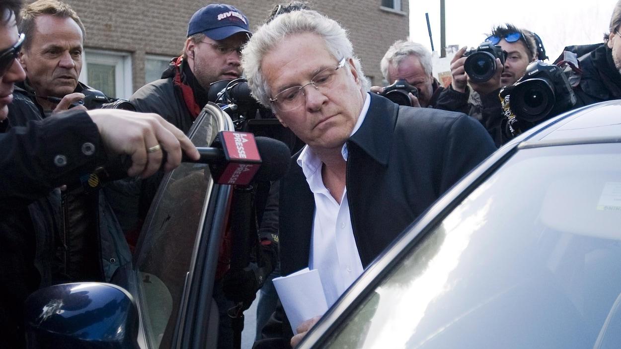 Tony Accurso entre dans une voiture côté passager, entouré de photographes de presse.