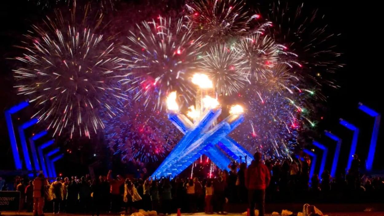 Des gens regardent les feux d'artifice et la flamme olympique.