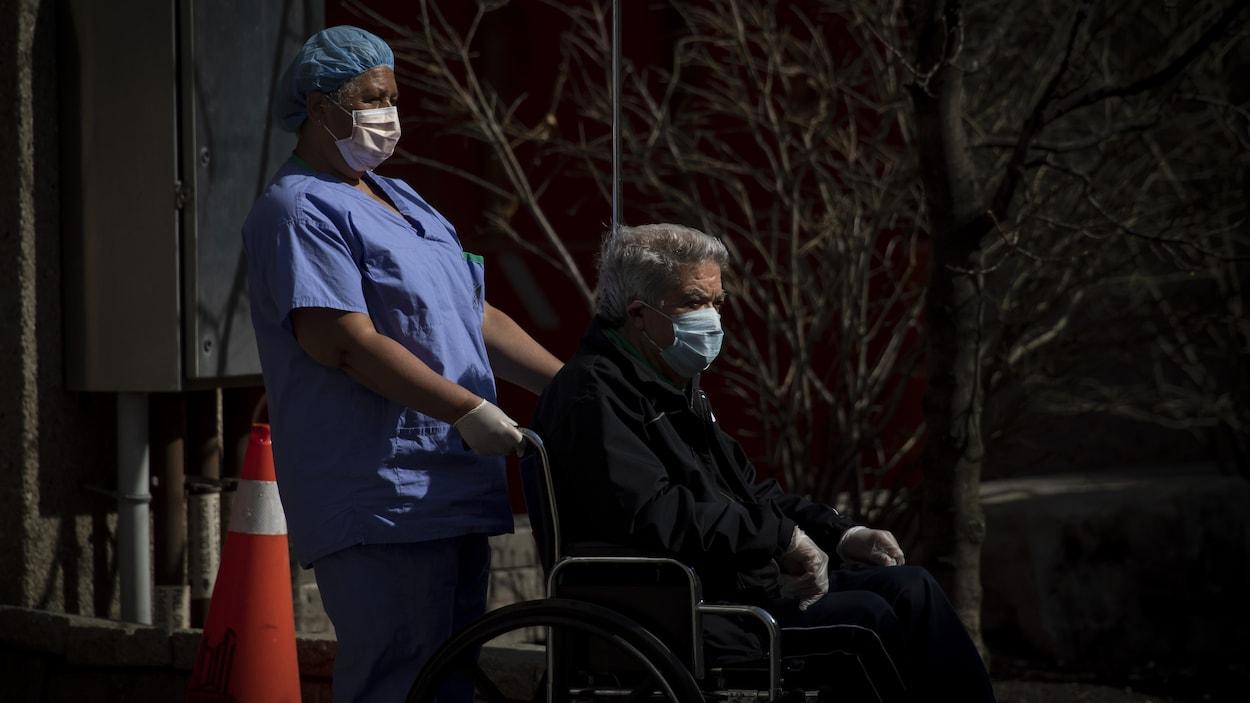 Une préposée promène un bénéficiaire en fauteuil roulant.