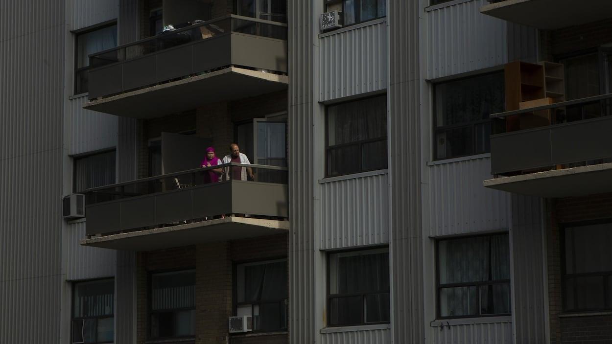 Un couple regarde à l'extérieur depuis le balcon de son appartement.