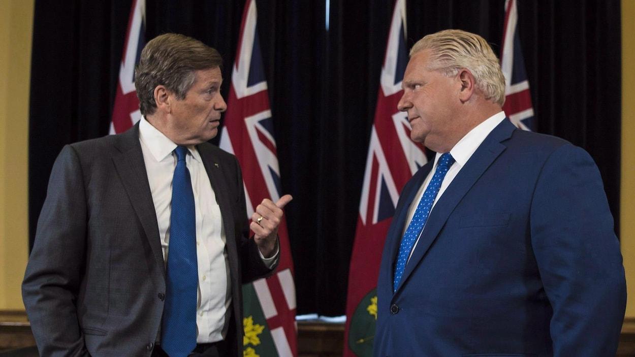 Deux hommes se parlent debout dans un bureau.