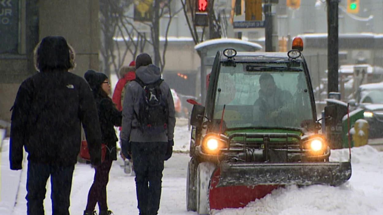 Un chasse-neige en train de déneiger une voie dans la ville.