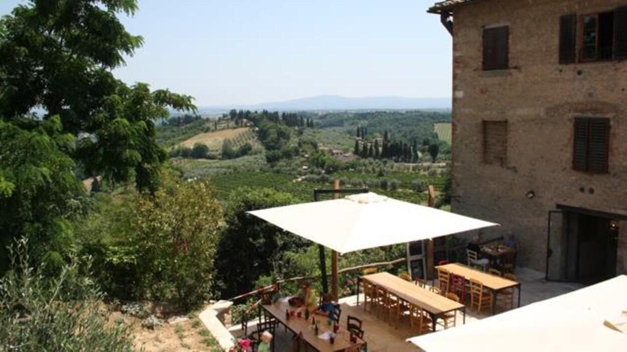 Paysage vallonneux de la Toscane, avec au premier plan une partie d'un vieux bâtiment de pierre et une terrasse sur laquelle on trouve deux grandes tables et des chaises protégées par un grand auvent.