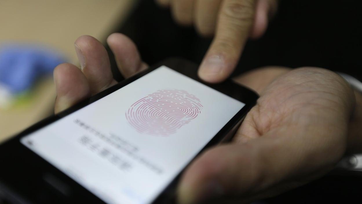 Une photo montrant les mains d'une personne qui tient un iPhone sur l'écran duquel est affichée une empreinte digitale. La personne appuie sur le lecteur d'empreintes digitales avec son index droit.