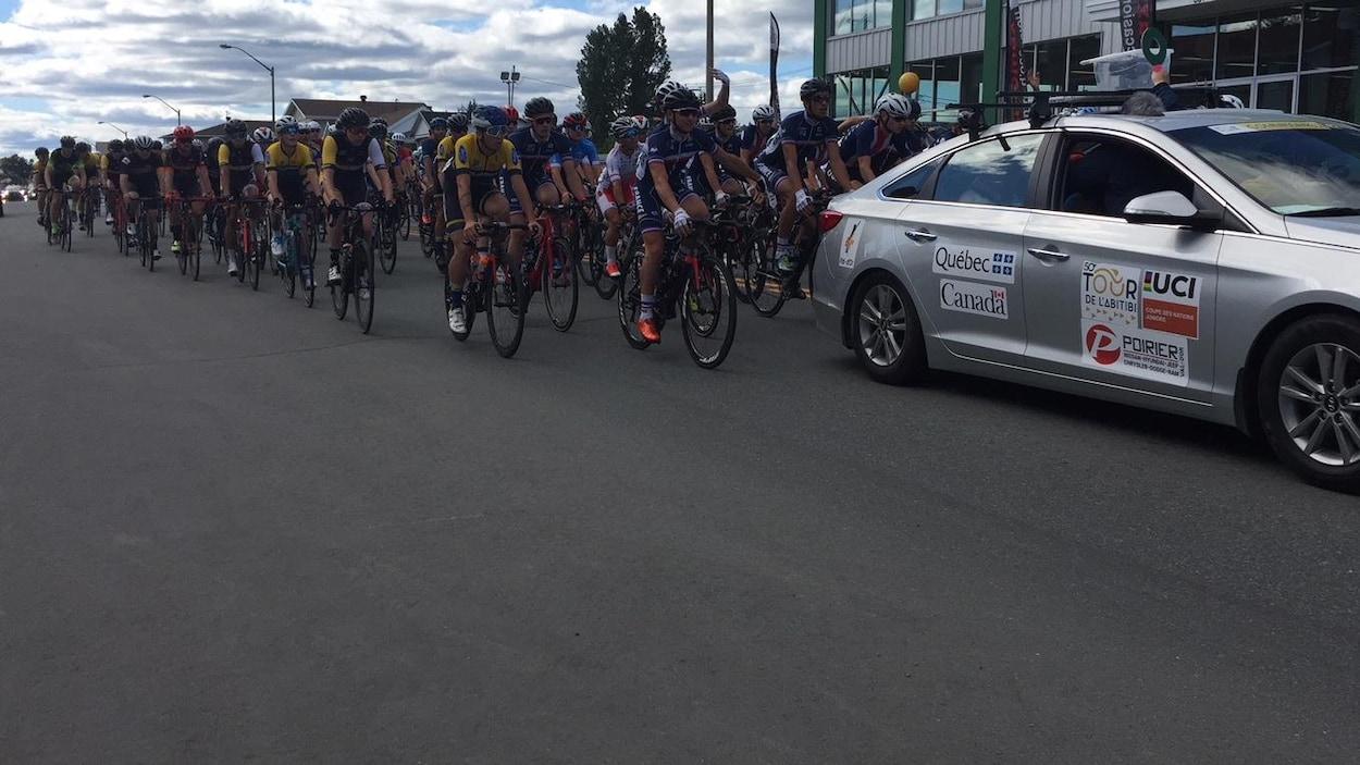 Un peloton de cyclistes serrés derrière le véhicule du Tour de l'Abibiti 2018.