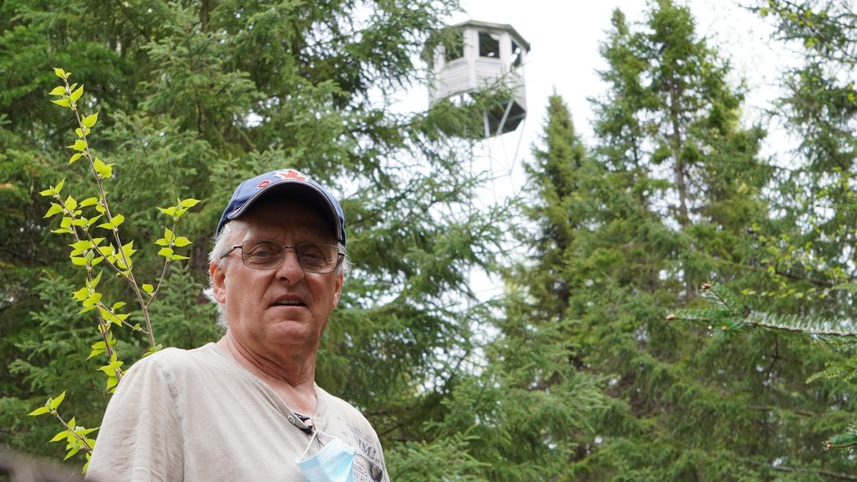 Un homme pose devant une tour de feu