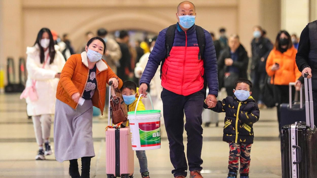 Les membres d'une famille chinoise munis de masques portent des valises.