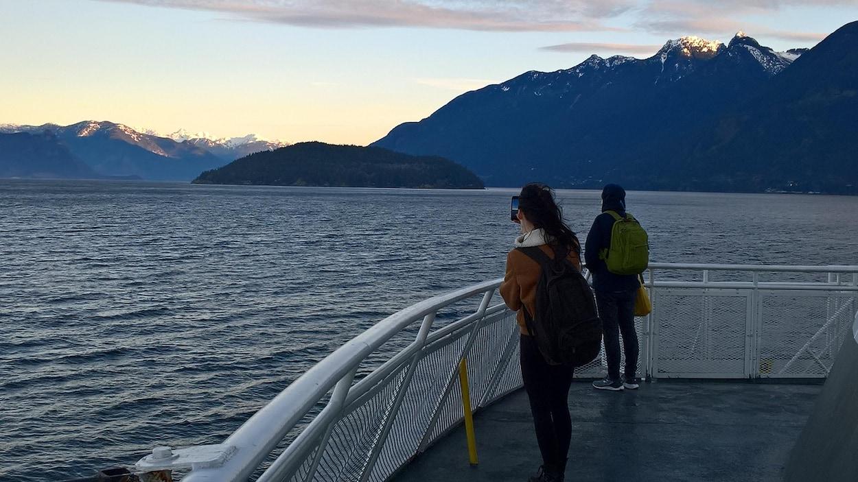 Deux passagers observent debout des montagnes enneigées depuis le pont d'un traversier qui quitte Horseshoe Bay en Colombie-Britannique.