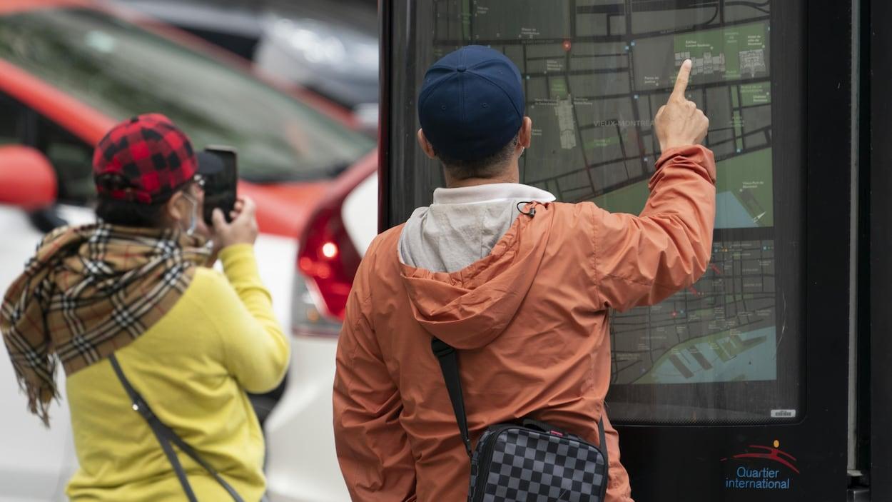Deux personnes de dos regardent une carte du centre-ville de Montréal.