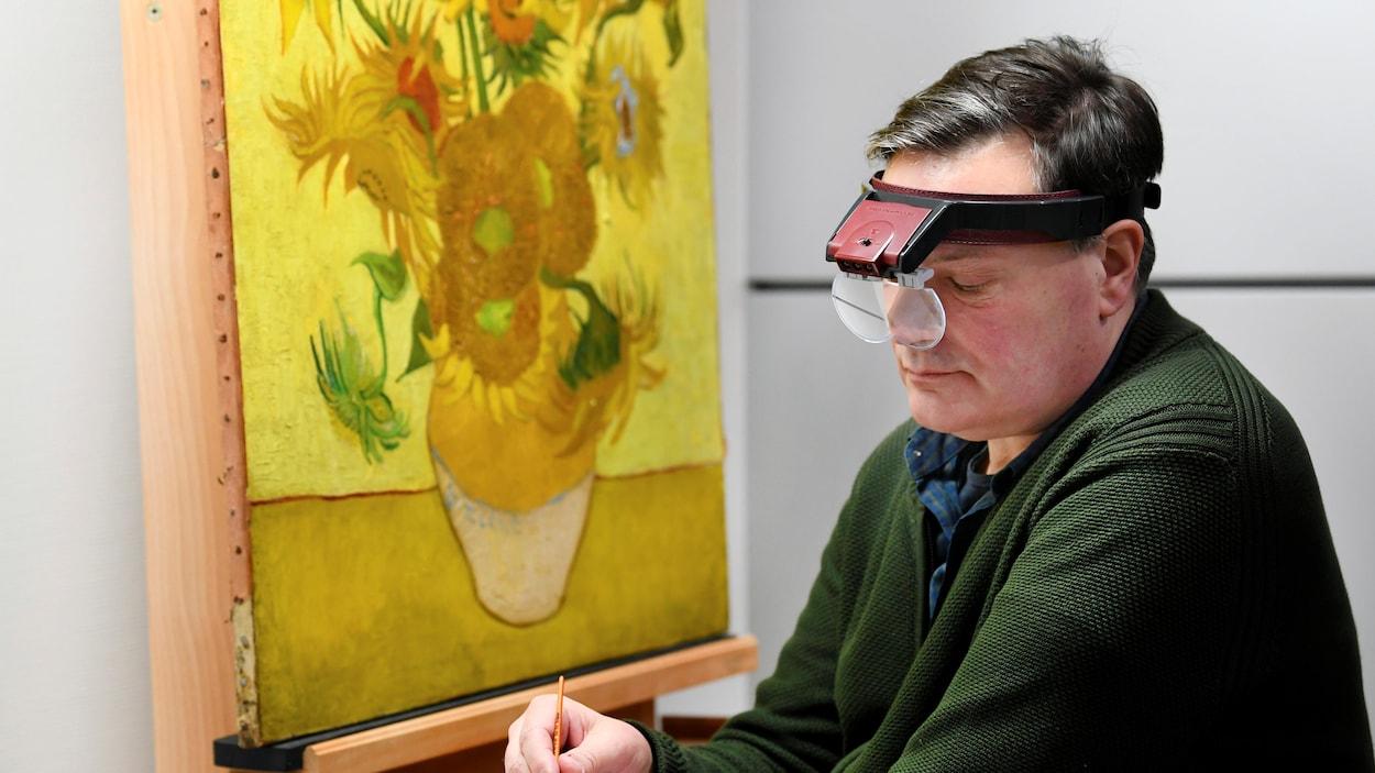 Un restaurateur, tenant un pinceau, restaure le tableau représentant des tournesols.