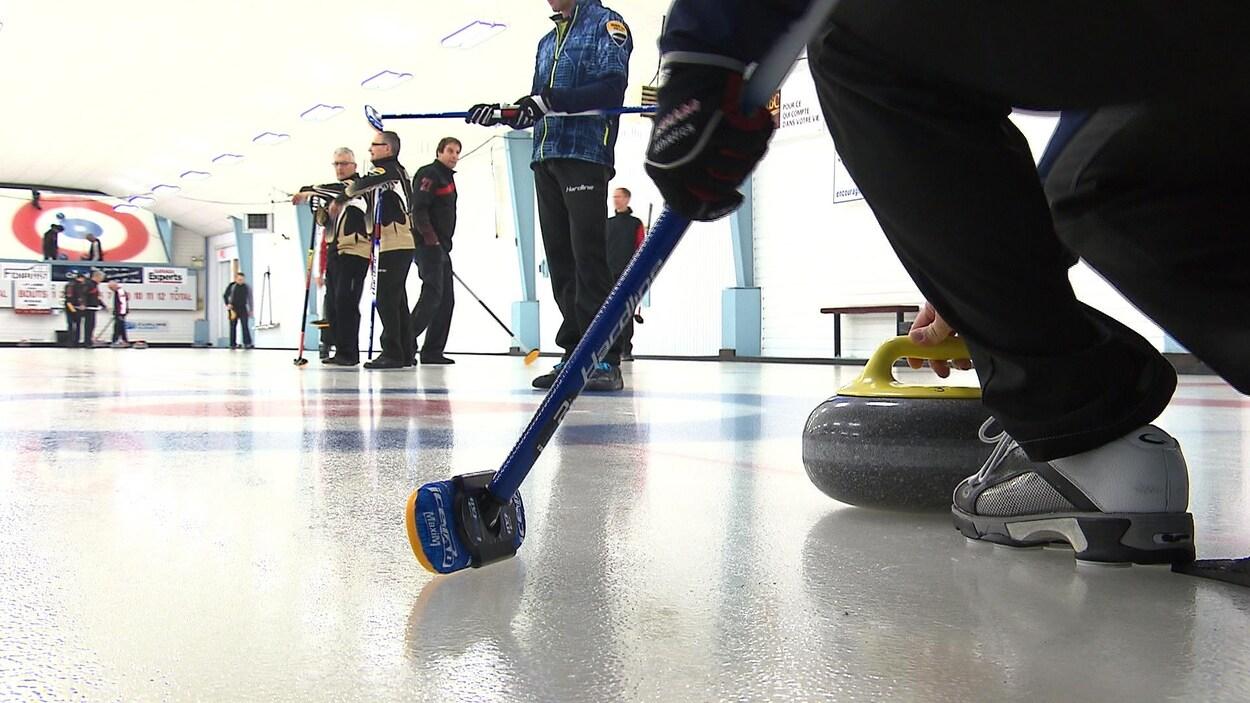 Lancement d'une pierre de curling alors que d'autres joueurs observent.