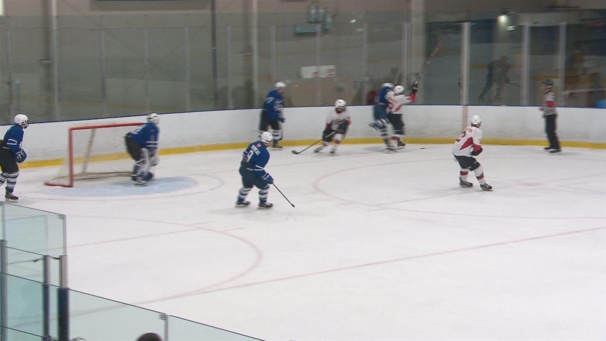Des jeunes jouent au hockey dans un aréna
