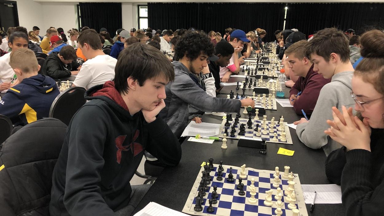 Une longue lignée de joueurs sont concentrés devant leur échiquier.