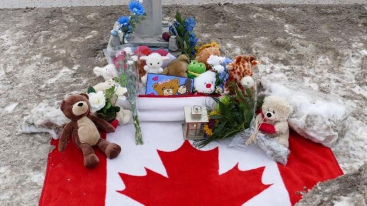 Des oursons, des fleurs et une chandelle reposent sur le drapeau du Canada.