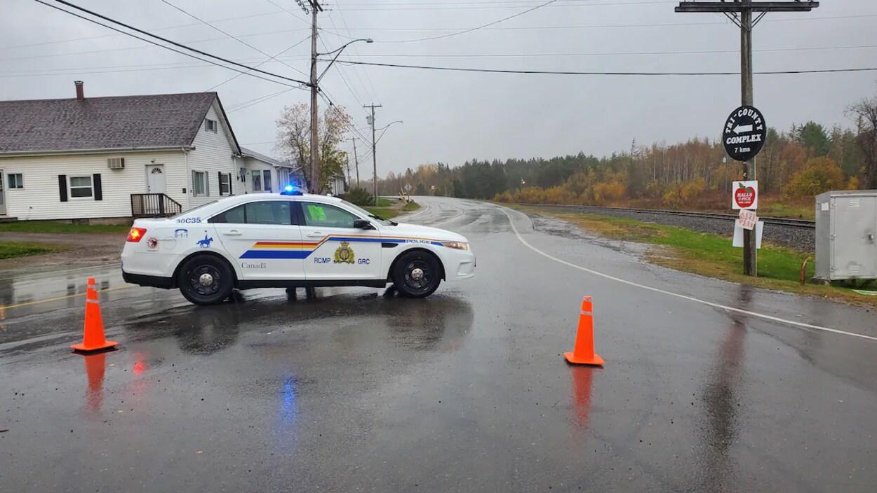Une voiture de la GRC stationnée en travers de la route, avec des cônes orange devant elle.