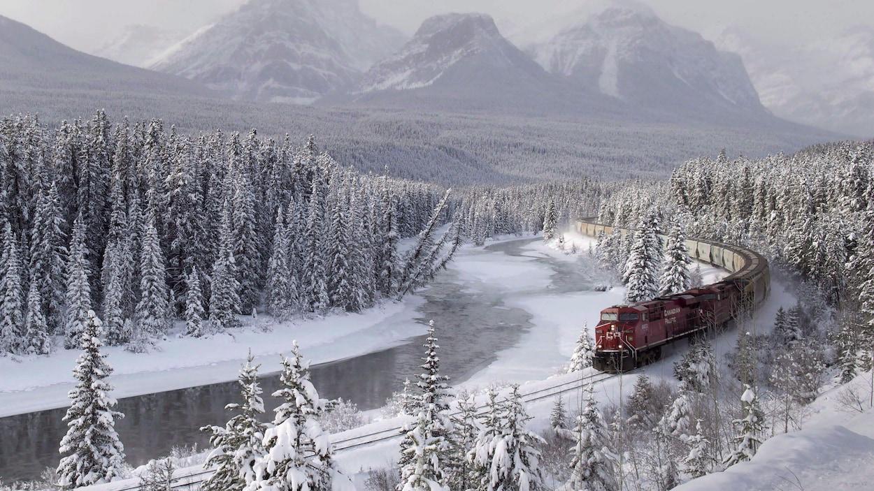 Un train rouge du Canadien Pacifique roule au milieu de sapins recouverts de neige et le long d'une rivière à moitié gelée. Au loin, on voit les sommets enneigés des Rocheuses.