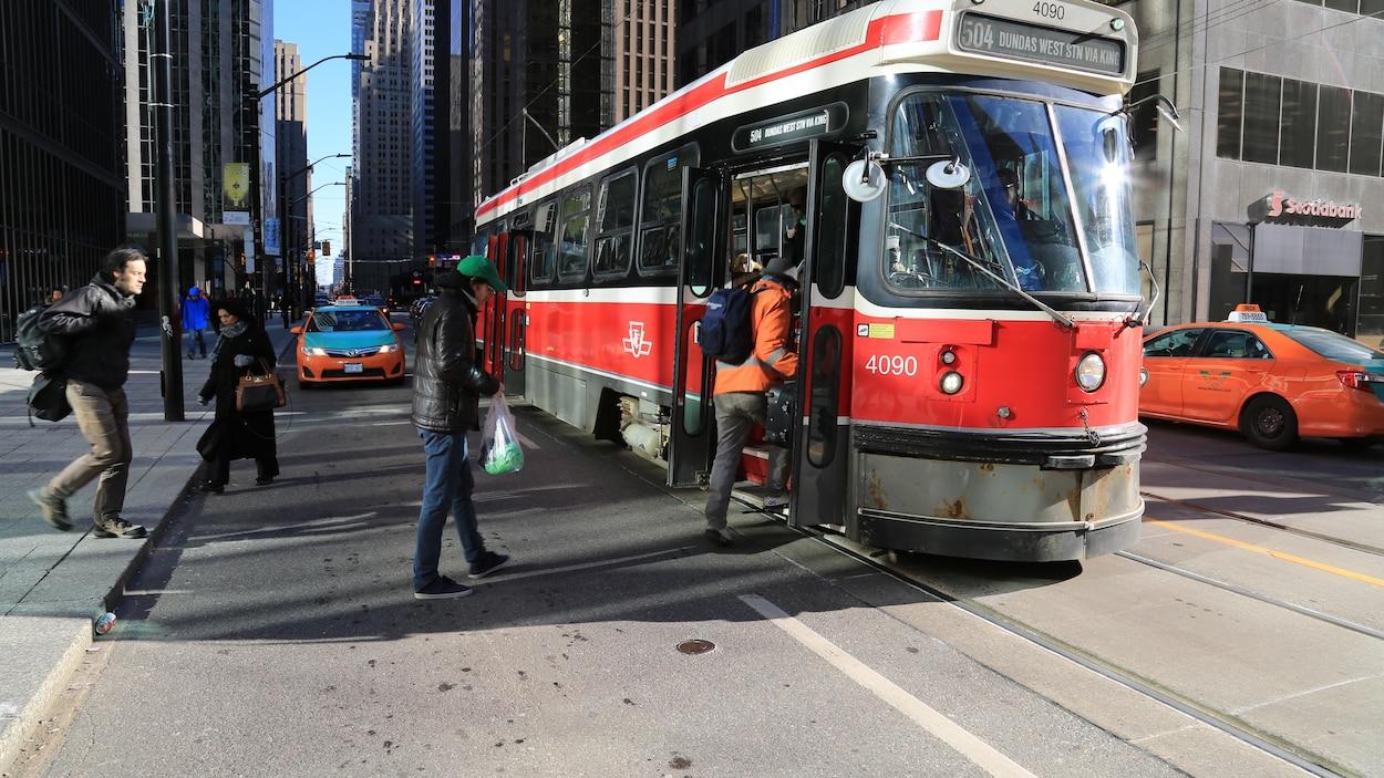 Des Torontois embarquent dans un tramway à un arrêt.