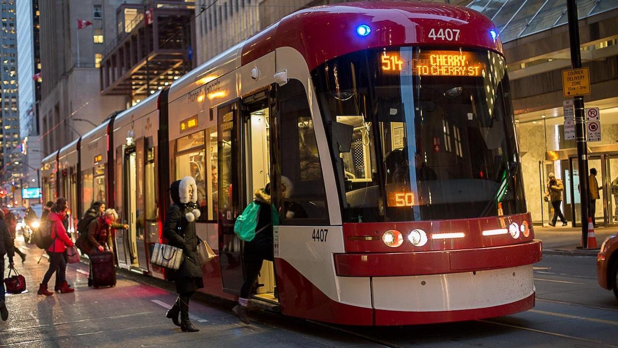 Photo de passagers qui montent à bord d'un tramway.