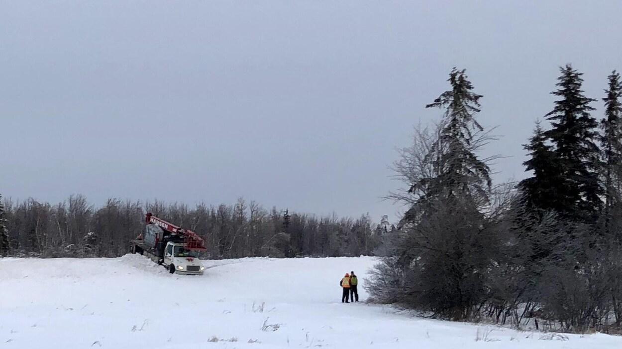 Deux hommes sur le bord de la route regardent un camion immobilisé dans la neige sur un talus.