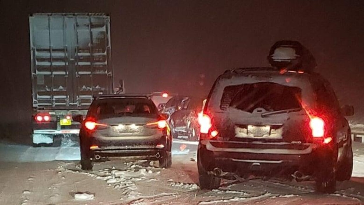 Des voitures et un camion sont immobilisés sur une autoroute glacée et enneigée.