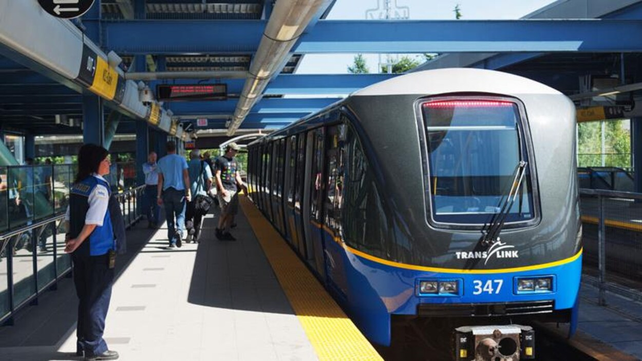 Un train du SkyTrain arrive dans une station.