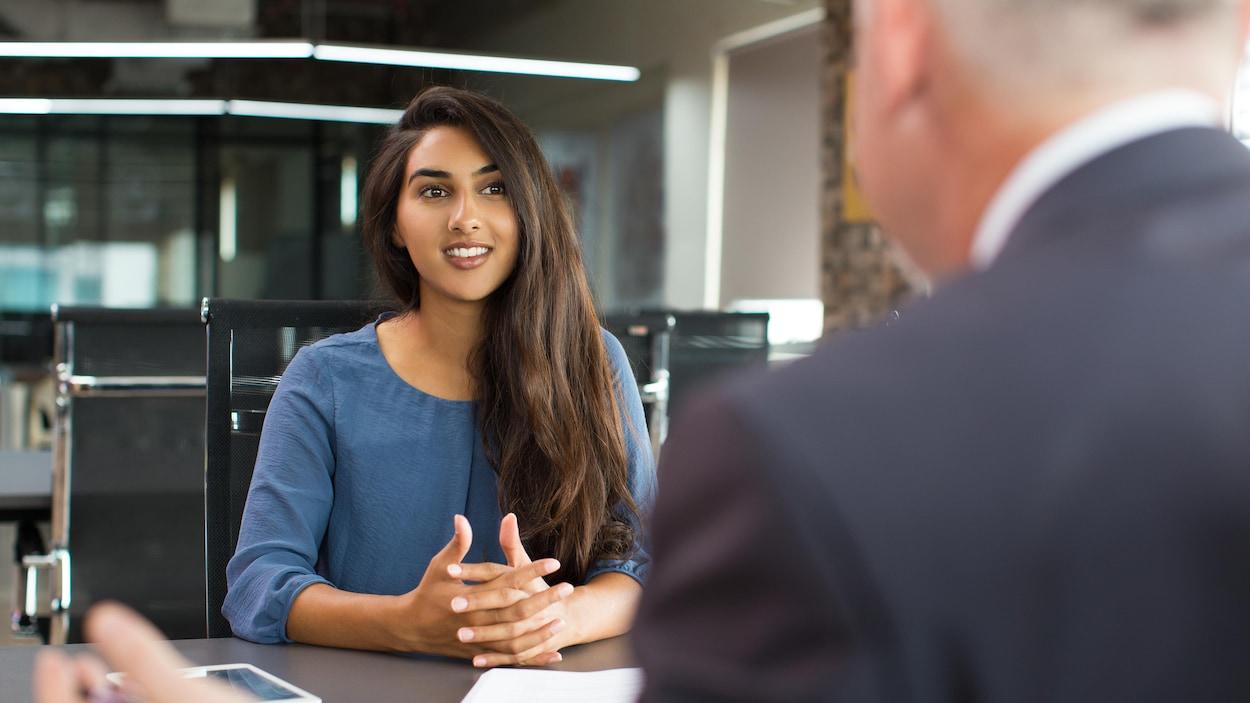 Une jeune femme sourit à un homme assise devant elle lors d'une réunion de travail.