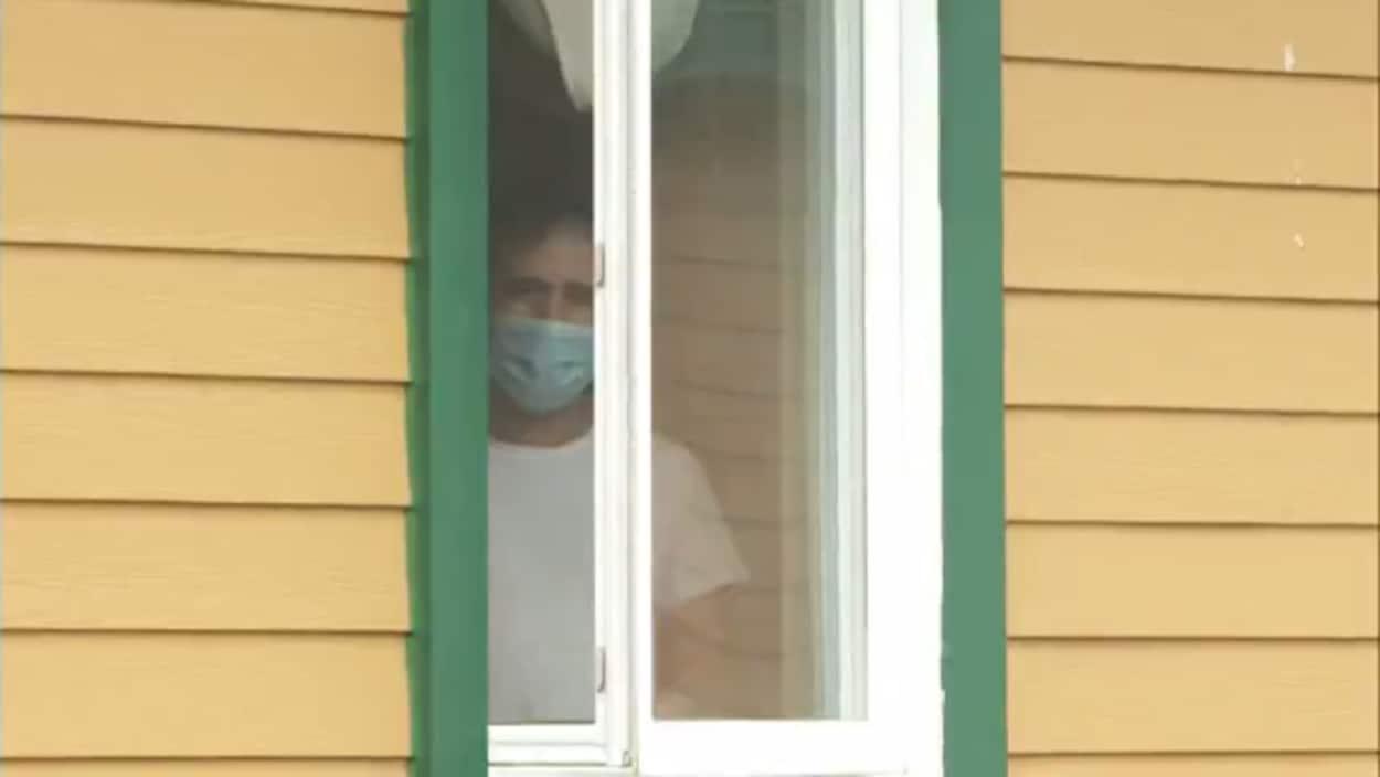 Un homme portant un masque regarde à travers une fenêtre.