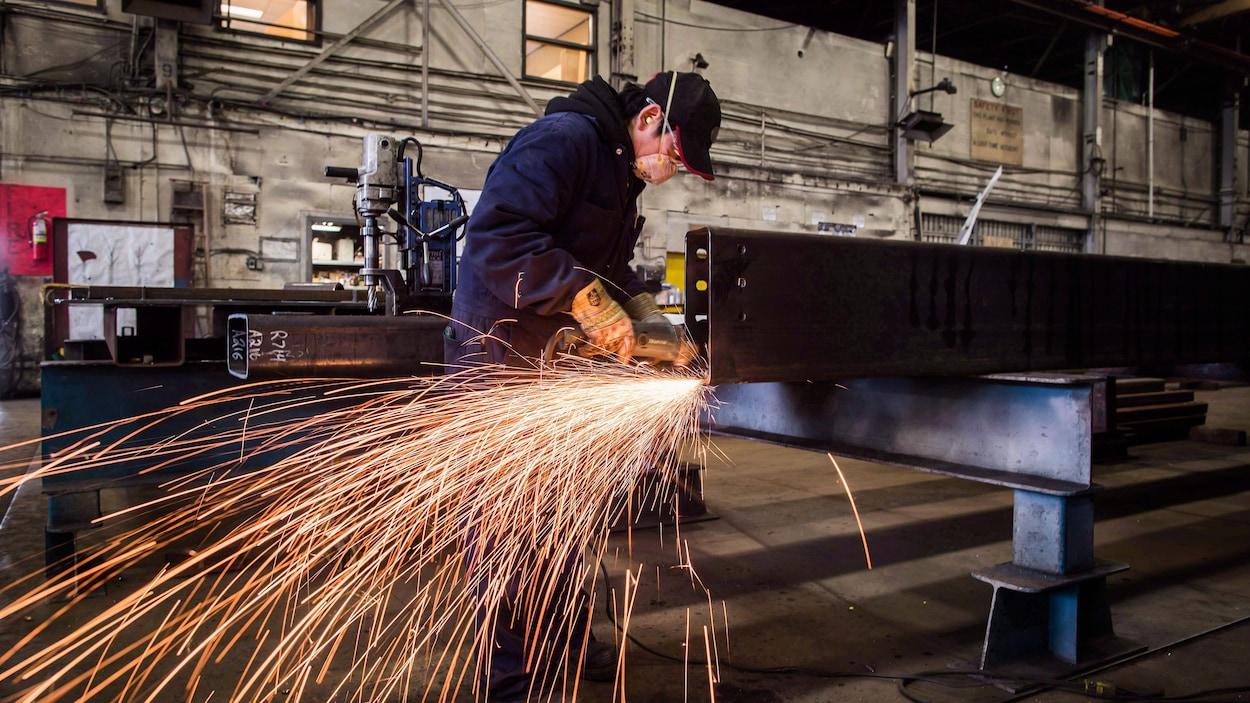 Un travailleur polit une pièce d'acier dans une aciérie de Colombie-Britannique.