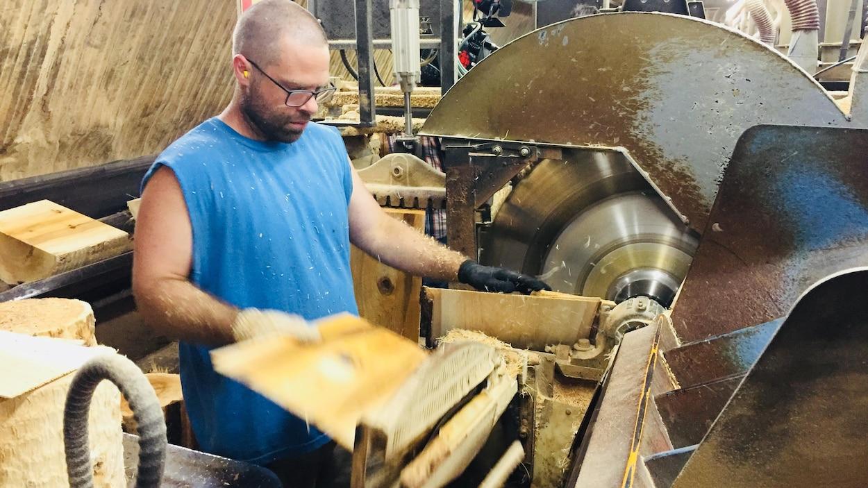 Un travailleur de la scierie Waska, au Nouveau-Brunwick, coupe des bardeaux de cèdre.
