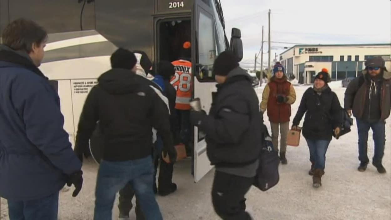 Des travailleurs d'Alma montent dans un autobus