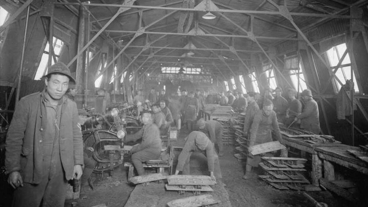 Ouvriers de la 51e Chinese Labour Company, dans un atelier du Corps de blindés. Teneur (village dans le Pas-de-Calais en France), printemps 1918.